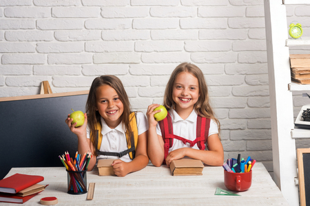 Little girls eat apple at lunch break. Friendship of small sisters in classroom at knowledge day. School time of girls. Happy school kids at lesson in september 1. Back to school and home schooling. Stock Photo