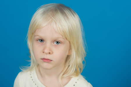 Kid with blonde hair. Little girl with young tender skin. Fashion style and beauty look. Childhood and happiness of innocent girl. Child with happy face and blond hair on blue background.