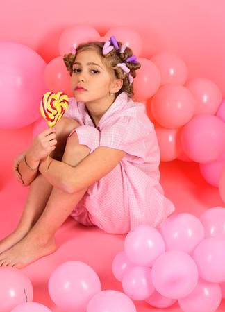Kind essen Lutscher auf rosa. Kind Mädchen mit Lockenwicklern im Haar Standard-Bild