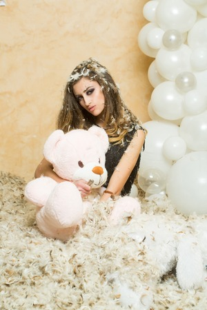 birthday anniversary gift. Woman rip teddy bear with knife. Sensual woman and animal doll in feather snowflakes. Bad behavior and aggression concept. Stock Photo