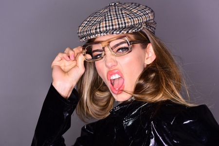 Sexy lady in stylish outfit, close up. Woman on scandalized face with make up wears checkered accessories and glasses for vision. Optics concept. Girl wears kepi, scarf and glasses, grey background. Stock fotó