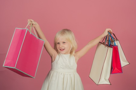 Birthday holiday celebration and party. small girl go shopping. Child smile with with paper bags in shop. Kid fashion and beauty look. punchy pastel trend. sale at black friday or cyber monday