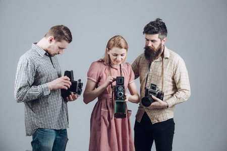 Men in checkered clothes, retro style. Company of busy photographers with old cameras, filming, working. Vintage fashion concept. Men and woman on pensive faces on grey background.