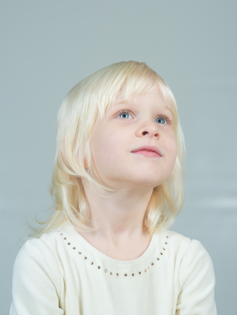 Kid with blonde hair. Fashion style and beauty look. Childhood and happiness of innocent girl. Child with happy face and blond hair on grey background. Little girl with young tender skin.