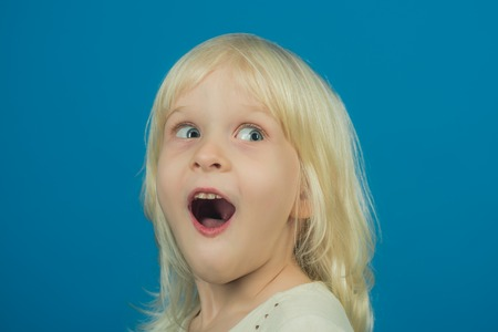 Child with happy face and blond hair on blue background. child with surprised hair in studio Foto de archivo