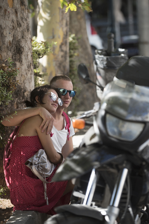 Couple in love sit in shadow of trees on hot summer day near parked motorbike, defocused. Refreshment concept. Couple hides out of sun, heat, hot, sitting, relaxing. Summer vacation, hot weather. Banco de Imagens