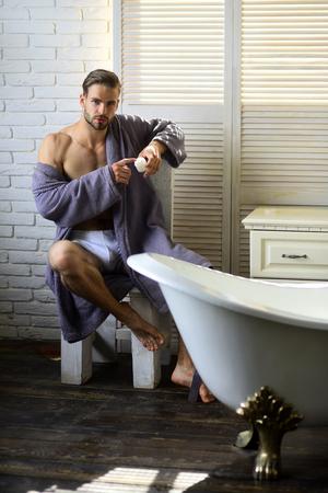 Gay with wax in bathrobe in bathroom. Body waxing, wax hair removal. Man beauty, grooming, hygiene, health. Foto de archivo - 100381075