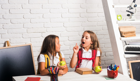 School time of girls. Little girls eat apple at lunch break. Happy school kids at lesson in september 1. Friendship of small sisters in classroom at knowledge day. Back to school and home schooling.