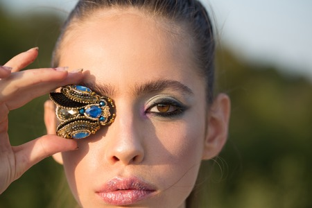 Woman with fly brooch jewelry at makeup face, look. Fashion look of stylish girl, makeup trend. Cosmetics for visage and skincare. Beauty and fashion girl. woman with handmade accessory. Stockfoto
