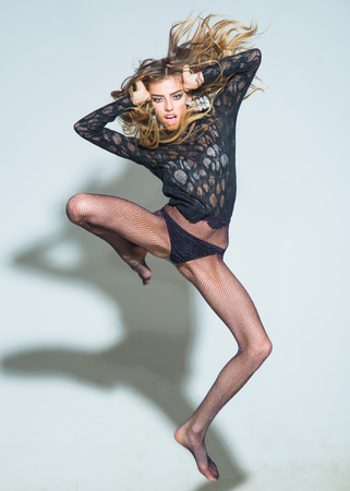 Fashionable sexy woman with long hair wearing lace top and tights, looks confident. Shampoo and hair care concept. Beautiful young woman jumping, puts hands on head, touching hair, grey background.