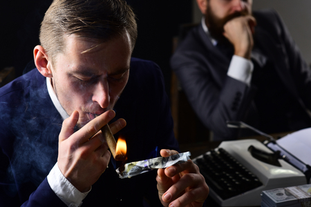 Man lighting cigar from burning banknote. Squander concept. Businessmen in suits sit at table with typewriter and money in dark interior, defocused. Businessman smoking cigar at business meeting.