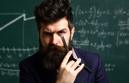 Bearded man is tutor or teacher. Education activities in classroom at school. Tutor will have to re-evaluate the students objectives. Great teachers find out what makes students interested.