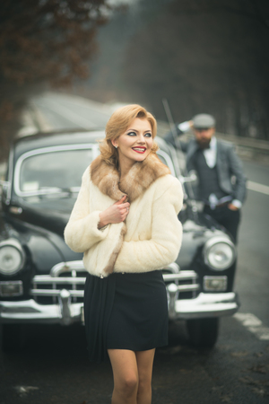 Retro collection car and auto repair by mechanic driver. Couple in love on romantic date. Travel and business trip or hitch hiking. Escort of girl by security. Bearded man and sexy woman in fur coat
