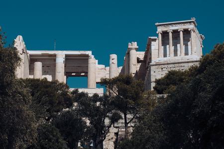 Vecchia costruzione con le colonne con la città moderna, fondo urbano. Tempio del greco antico circondato dal parco o dalla foresta. Concetto di patrimonio culturale e architettonico. Archivio Fotografico - 99958573