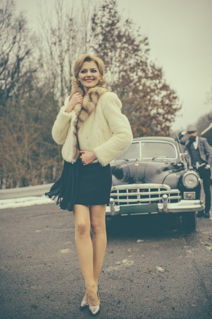 Woman walks on road. Couple in love on romantic date. Retro collection car and auto repair by mechanic driver. Bearded man and sexy woman in fur coat. Travel and business trip or hitch hiking Banque d'images