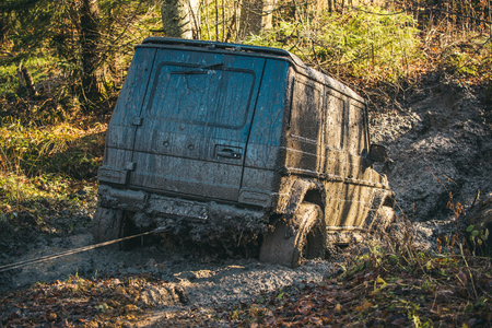 Crossover on nature background, reverse, back view. Extreme entertainment concept. Dirty offroad car stuck in dirt on sunny autumn day. SUV with car winch on countryside road. Reklamní fotografie