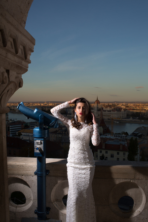 Woman with telescope at viewpoint on cityscape. Woman with long hair in white wedding dress, fashion Stok Fotoğraf - 101153980