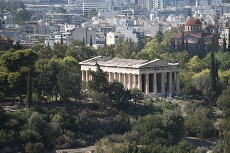 Ruins of ancient Greek temple surrounded by park or forest. Old building with columns with modern city, urban background. Confrontation of ages. Cultural and architectural heritage. Archivio Fotografico - 100377614