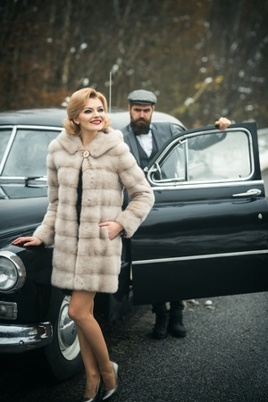 Bearded man and sexy woman in fur coat. Escort of girl by security. Retro collection car and auto repair by mechanic driver. Travel and business trip or hitch hiking. Couple in love on romantic date Stock fotó