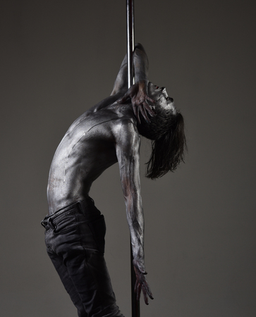 Guy with nude torso covered with shimmered sweat or paint hanging on metallic pole. Young strong pole dance man on dark background.