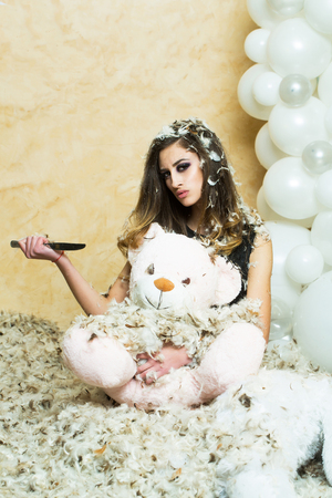 Sensual woman and animal doll in feather snowflakes. Woman rip teddy bear with knife. Christmas, new year or birthday anniversary gift. Bad behavior and aggression concept.