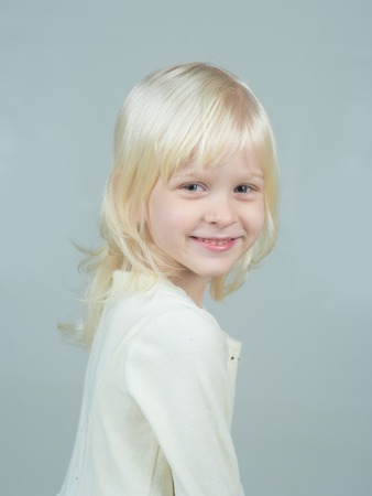 Little girl with young tender skin. Child with happy face and blond hair on grey background. Fashion style and beauty look. Kid with blonde hair. Childhood and happiness of innocent girl.