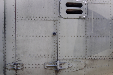 Old silver metal surface of the aircraft fuselage with rivets. Fuselage detail view. Airplane metallic fuselage detail with rivets. Standard-Bild
