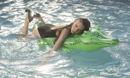 girl on inflatable mattress crocodile in the pool