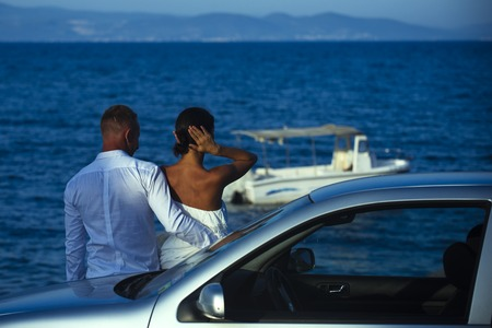 Couple in love stand near silver car, sea on background. Couple arrived on vacation, honeymoon. Man and woman looking at sea and boat, enjoy view. Romantic walk of couple near sea. Luxury rest concept