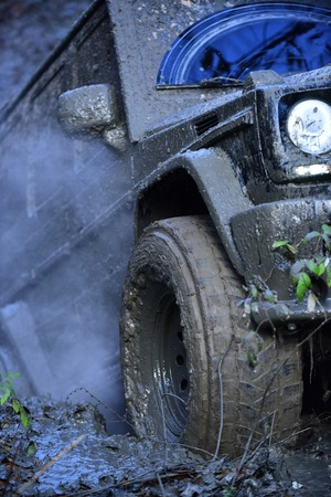 Part of SUV stuck in dirt, close up. Dirty offroad tire covered with mud. Wheel with cloud of smoke, defocused. Dirty offroad car overcomes obstacles in forest area. Impassibility of roads concept.