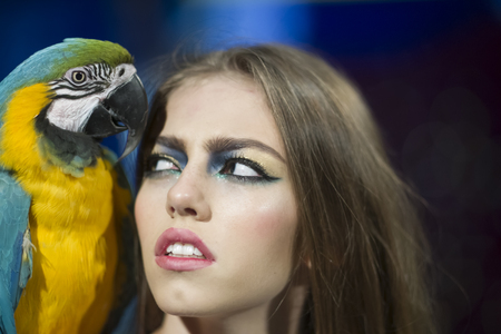 Sensual woman look at parrot. Woman with blue and yellow macaw. Sexy girl with makeup and bird pet. Beauty model with exotic ara animal. Friends and friendship.