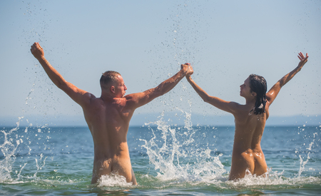 Sexy woman and man are free. Couple in love with sexy body relax on beach. Summer holidays and paradise travel vacation. Love relations of naked couple in sea water. happy family or valentines day Stockfoto