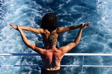 Attractive couple feel free and enjoy summer vacation. Freedom concept. Nude couple stands on deck of cruise liner with sea waves on background, rear view. Couple in love travelling on cruise ship. Reklamní fotografie