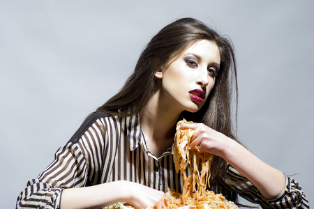 Beauty model with makeup and long brunette hair have dinner. Sexy woman eat spaghetti with hands. Woman eat pasta dish with tomato ketchup. Hungry girl have italian food meal. Food, diet and cuisine. Stockfoto