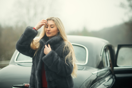 Flirty and glamorous woman with black retro car Banque d'images