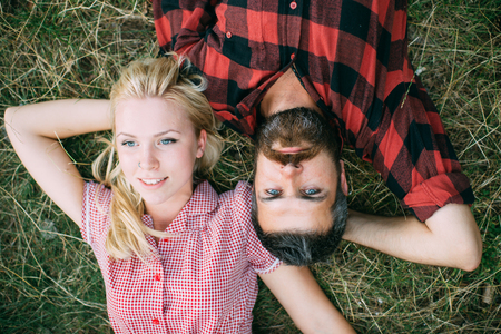Romantic couple lying on grass in park. Blond woman and bearded man relaxing with arms bent and hands beneath their heads view from above. Summer holiday romance.
