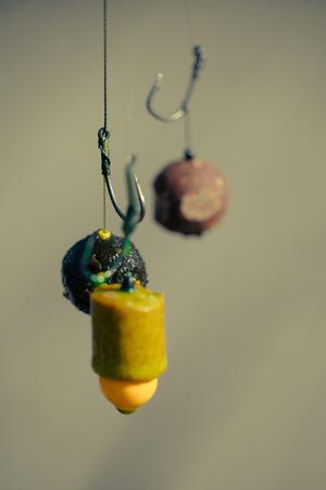 Fishhooks on line on blurred background. Hooks with fishing bait, chumming. Fishing, angling, catching fish, chum.