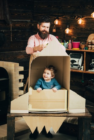 Kid happy sit in cardboard hand made rocket. Parenthood concept. Boy play with dad, father, little cosmonaut sit in rocket made out of cardboard box. Child boy play cosmonaut, astronaut.