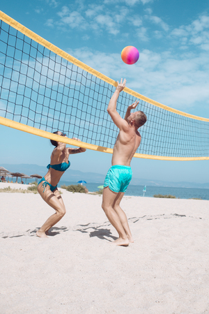 Beach volleyball concept. Couple have fun playing volleyball. Young sporty active couple beat off volley ball, play game on summer day. Woman and man fit, strong, healthy, doing sport on beach.