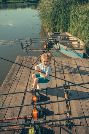 Boy with fishing rod catching fish in the summer. Concept for childhood, healthy lifestyle and vacation