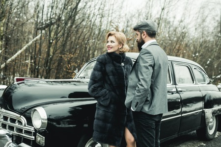 Escort of girl by security. Bearded man and sexy woman in fur coat. Retro collection car and auto repair by mechanic driver. Couple in love on romantic date. Travel and business trip or hitch hiking