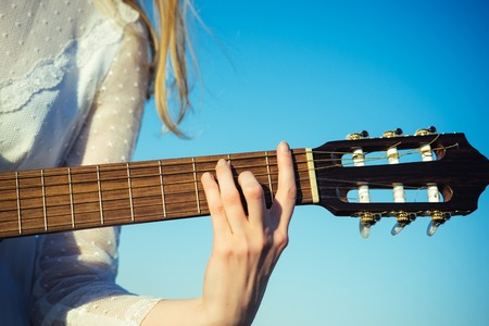 Entertainment, guitar with fingers strumming strings. Entertainment hand play on string instrument on blue sky. Stock Photo