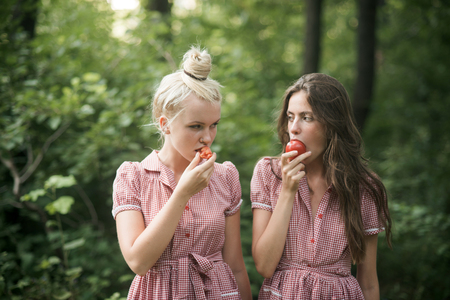 Camping in woods. Beautiful young girls wandering in forest. Two sisters in vintage dresses eating juicy tomatoes. Vitamins, nutrition and healthy diet concept. Фото со стока