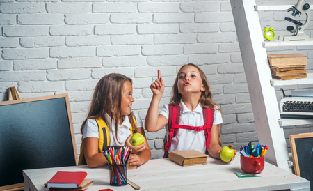 School time of girls. Friendship of small sisters in classroom at knowledge day. Little girls eat apple at lunch break. Happy school kids at lesson in september 1. Back to school and home schooling.