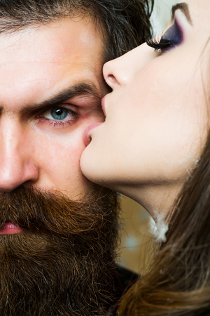 Woman kiss bearded man with love. Woman with makeup skin and hipster with long beard. Stok Fotoğraf