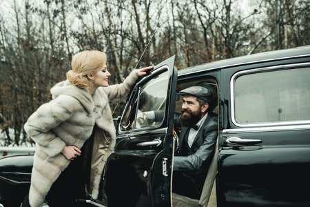 Bearded man and sexy woman in fur coat. Couple in love on romantic date. Travel and business trip or hitch hiking. Retro collection car and auto repair by mechanic driver. Escort of girl by security