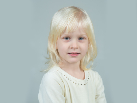 Childhood and happiness of innocent girl. Fashion style and beauty look. Kid with blonde hair. Child with happy face and blond hair on grey background. Little girl with young tender skin.