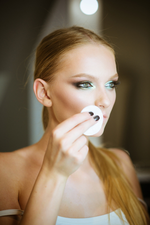Makeup removal and application. Makeup model use cotton pad.
