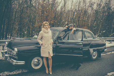 Escort of girl by security. Travel and business trip or hitch hiking. Couple in love on romantic date. Bearded man and sexy woman in coat. Retro collection car and auto repair by mechanic driver