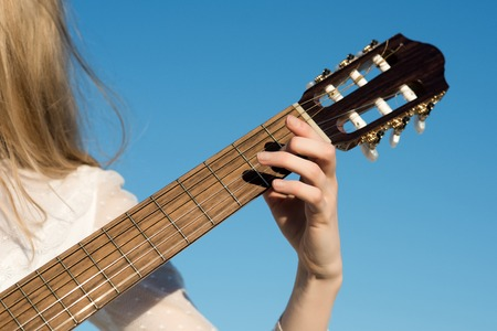 Hand play on string instrument. Guitar with fingers strumming strings. Classic guitar neck fretboard and headstock on sunny blue sky. Music and entertainment concept. Stock fotó